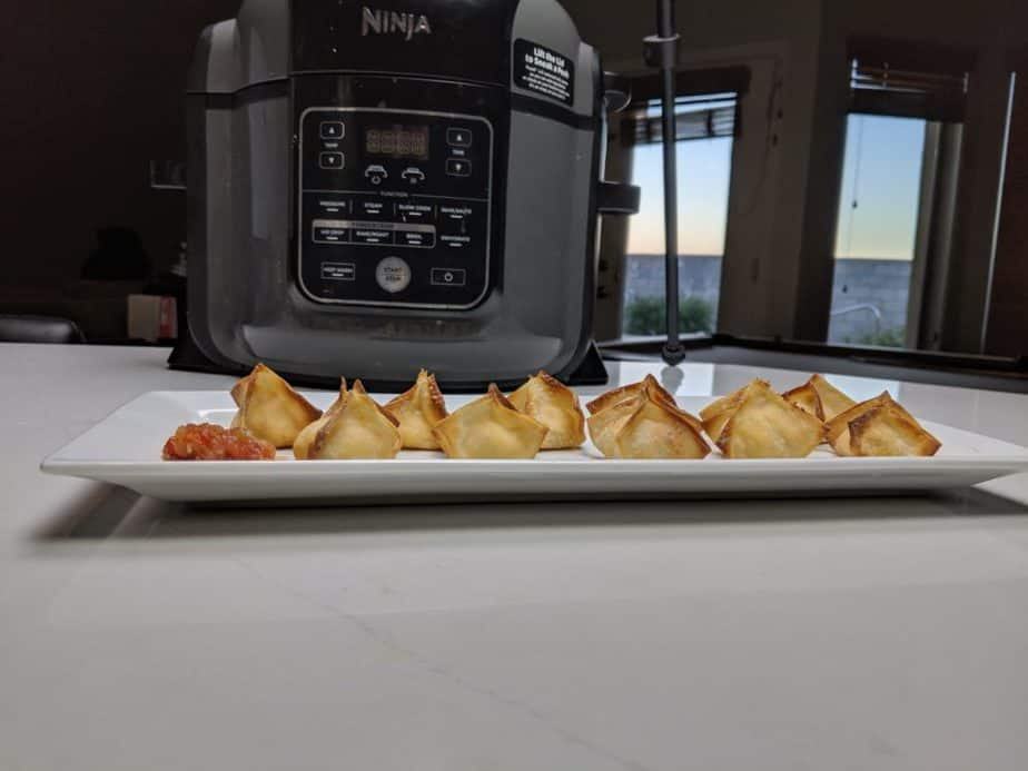 Buffalo Chicken Wontons with salsa in front of a Ninja Foodi