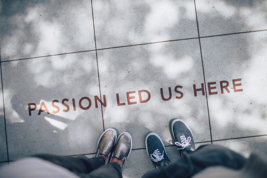 "2 people standing on a sidewalk where there is written ""Passion led us here"""