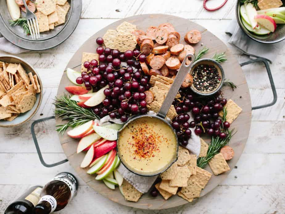 fruit,apple slices,crackers,and a sauce on a plate