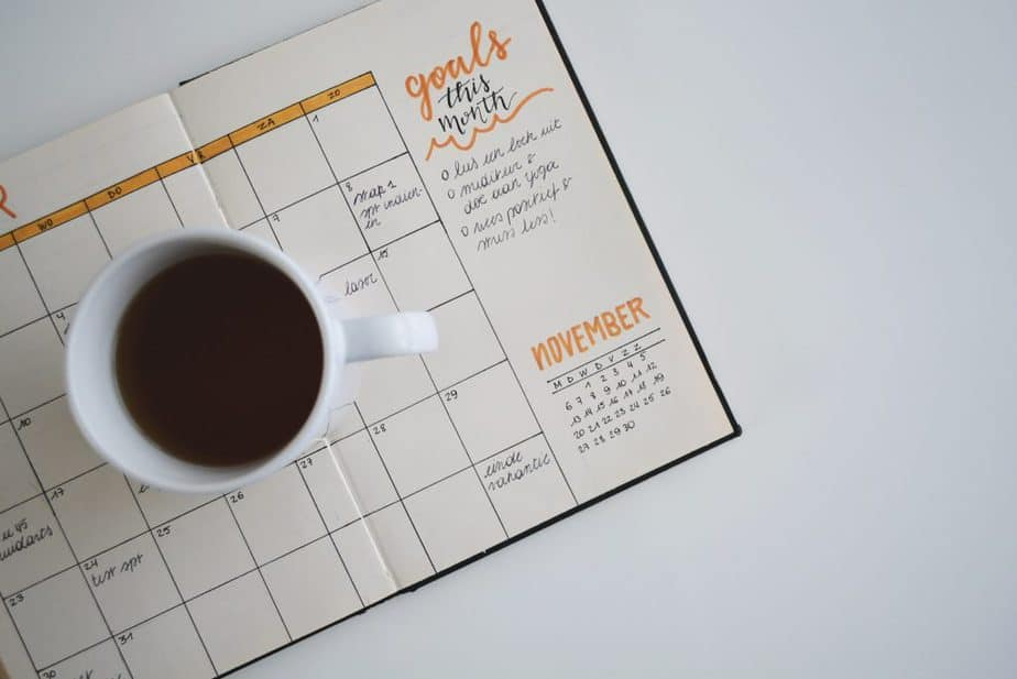 white ceramic mug with a liquid in it on top of a planner