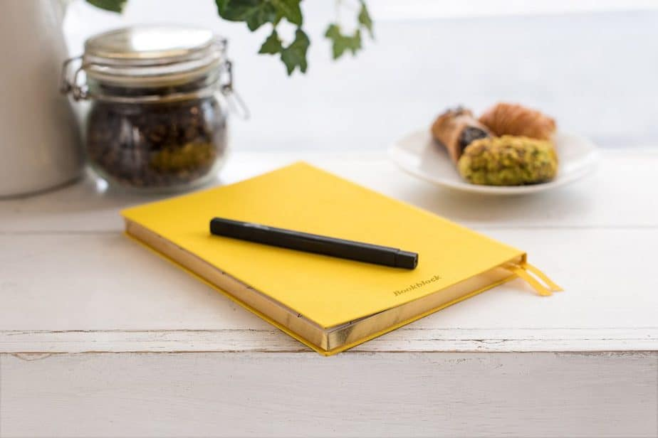 Yellow journal on a counter with a black pen.