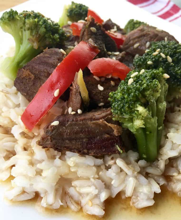 Beef and Broccoli over rice with a red pepper slice on top