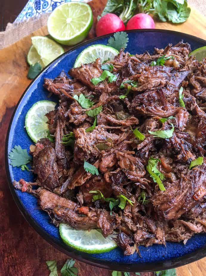 mexican shredded beef on a blue plate with lime slices and cilantro as a garnish