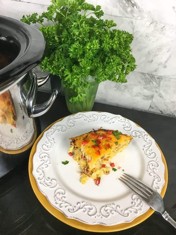 Slow Cooker Southwestern Breakfast Casserole wedge on a white plate with a fork. A vase with greenery in the background next to a slow cooker