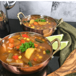 Vegetable soup in 2 copper bowls on a black table with 2 lime wedges between the two bowls