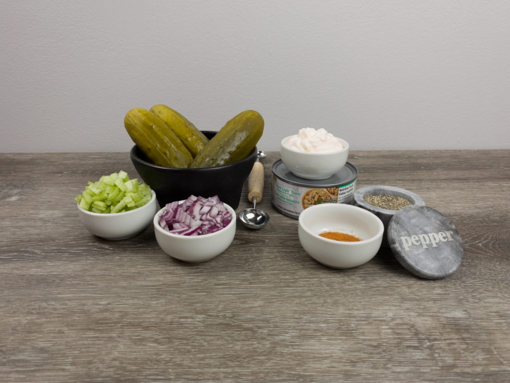 Ingredients for pickle tuna boats. chopped celery in a white bowl,chopped red onions in a white bowl, mayo in a white bowl, paprika and pepper in a white bowl, an unopened can of tuna and 3 pickles in a large black bowl.