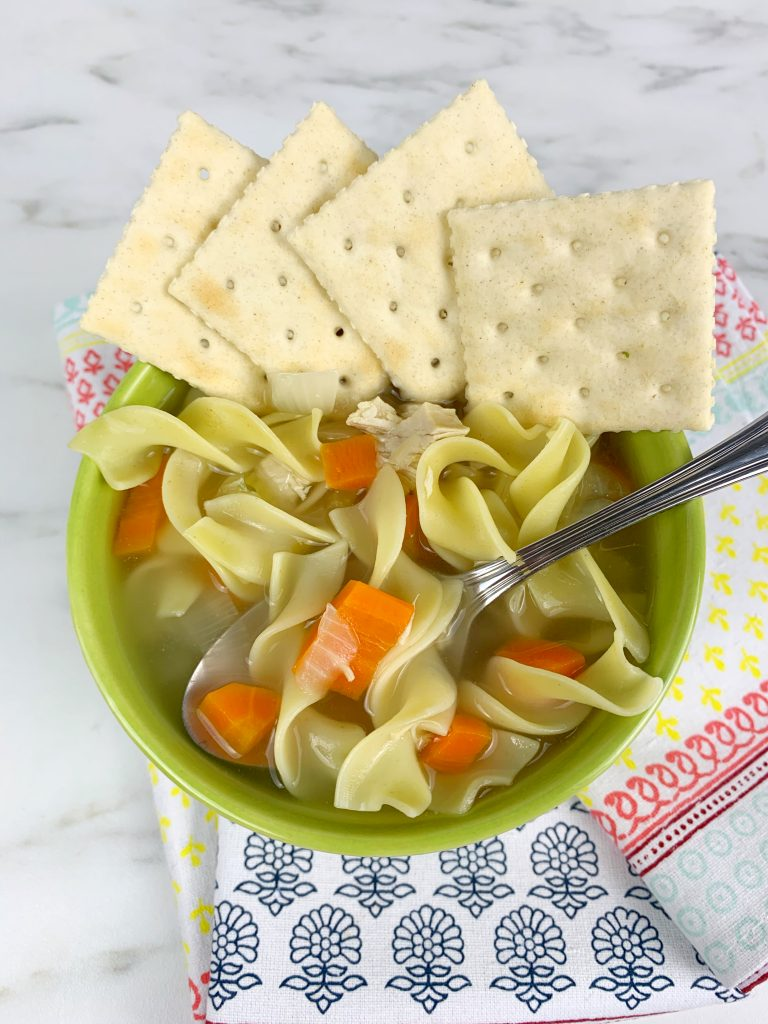 On a white marble table, there's a napkin with colorful designs. On top of the napkin is a green bowl with chicken noodle soup. There's a spoonin the bowl and crackers on top of the bowl.