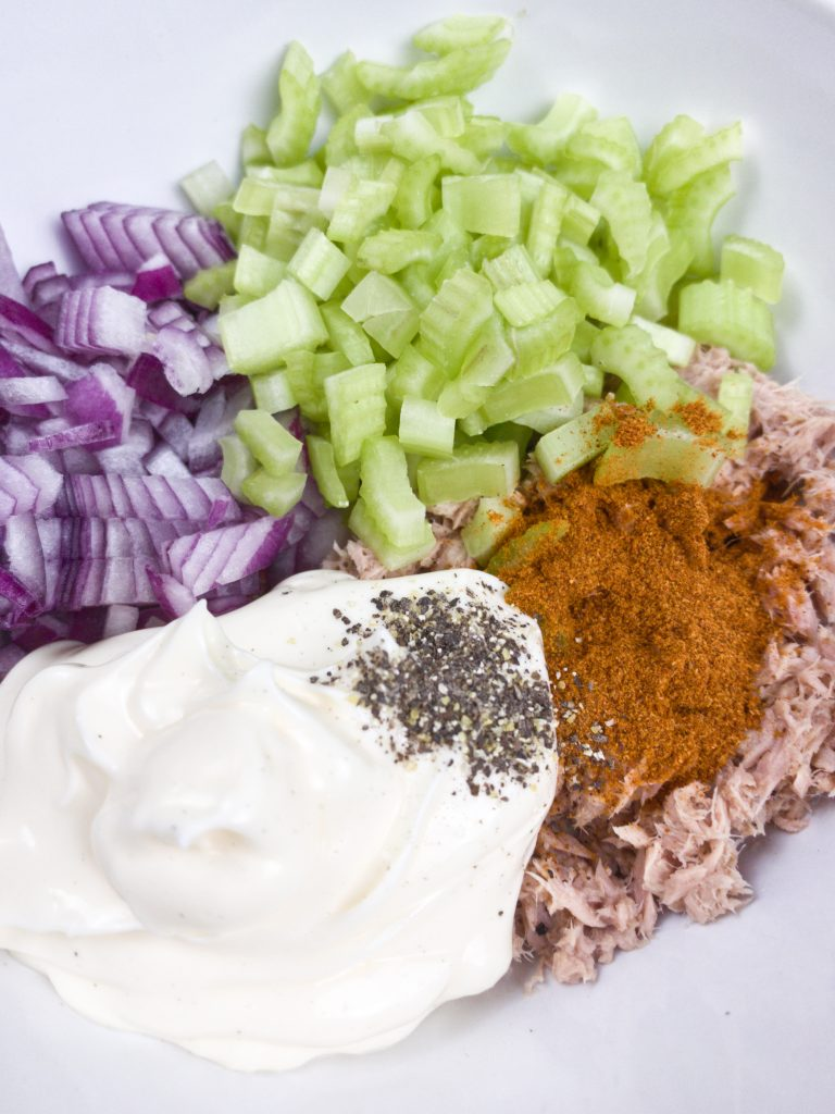 A plate with chopped onions and celery, mayo and tuna on it. spices are on top of the tuna and pepper is on the mayo.