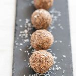Peanut butter balls on a slate with coconut shavings
