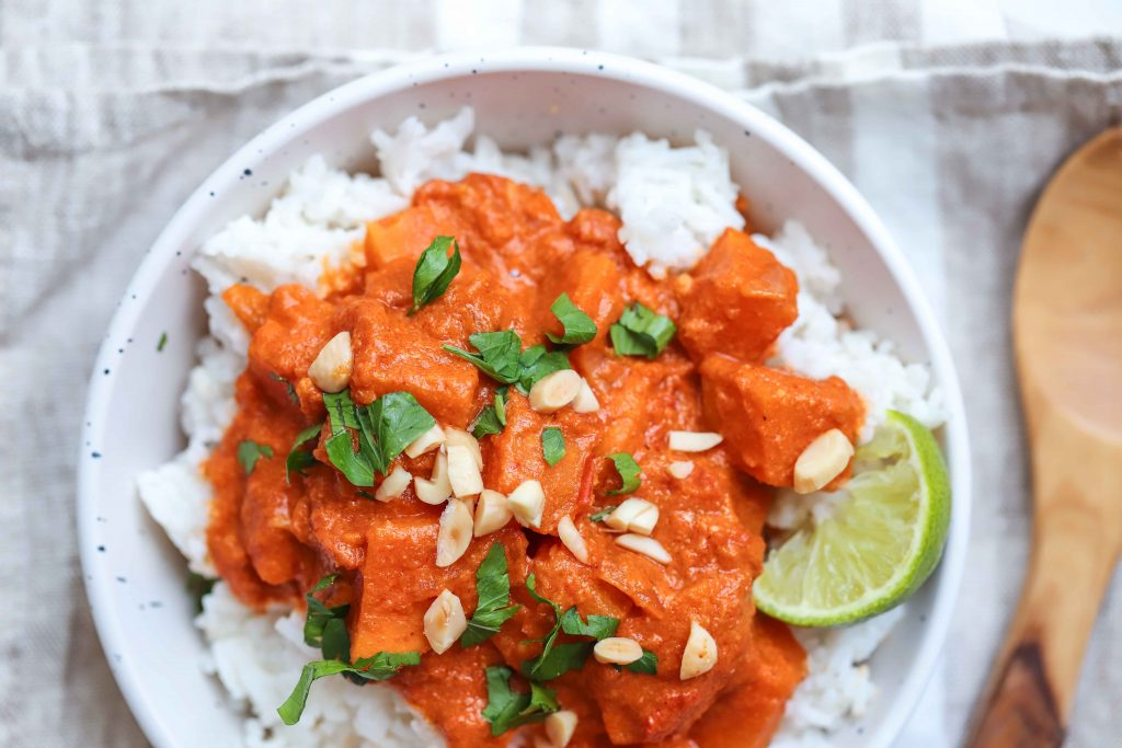 Sweet potato curry in a white bowl over rice. with a wooden spoon on the right. how to make red sweet potato curry