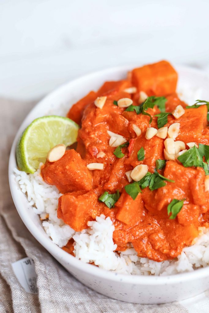 red sweet potato curry over white rice in a white bowl