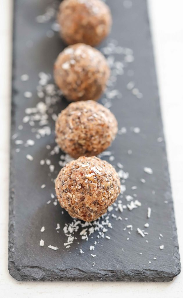 Protein balls on a serving slate with coconut shavings