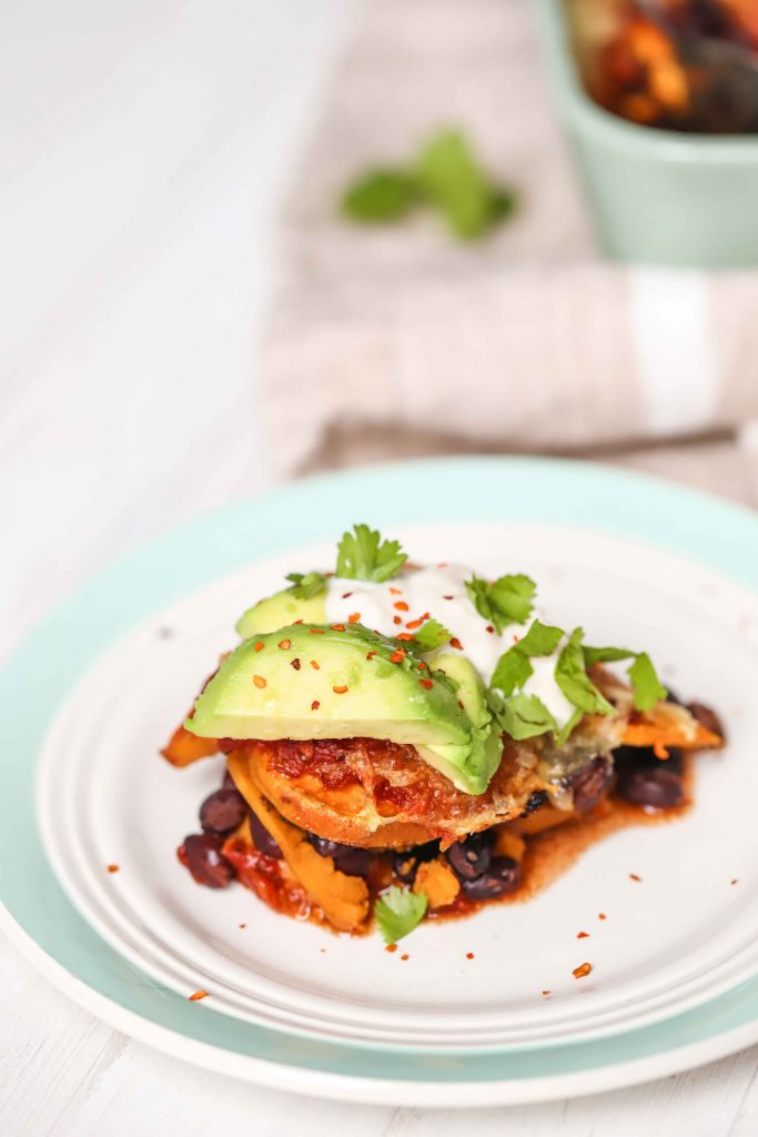 a piece of sweet potato and black bean casserole on a green and white plate garnished with avocado and red pepper flakes