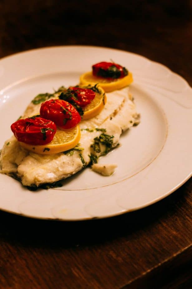 Baked fish with lemons and peppers on a white plate