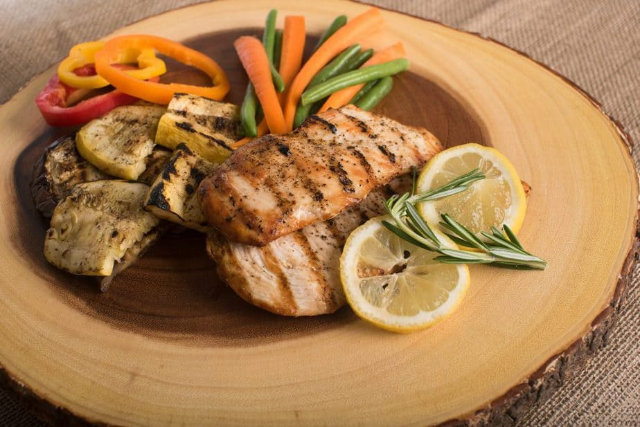 Chicken on a wood cutting board with veggies