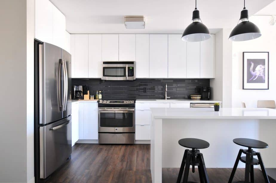 White kitchen with a silver microwave and silver fridge