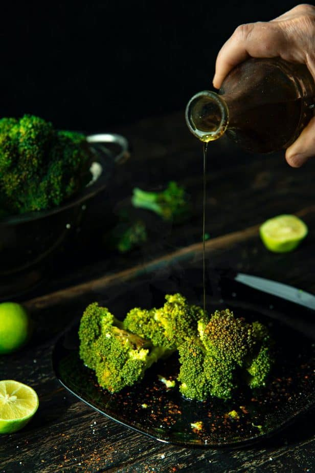 man pouring oil on a broccoli spear on the grill