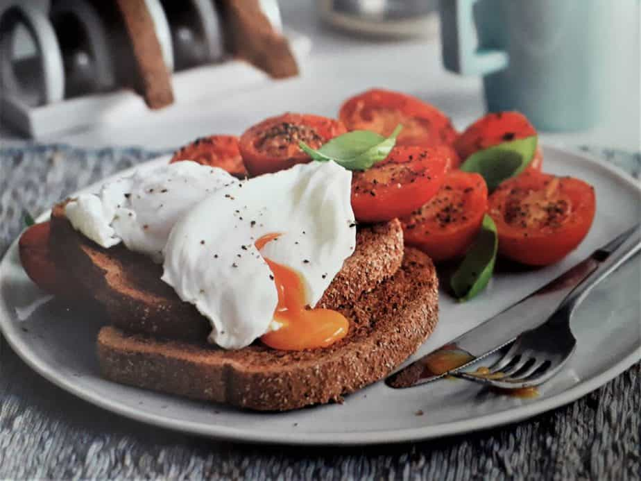 poached egg sandwich with tomatoes and whole grain bread