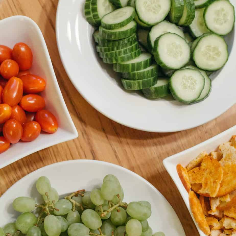 Green grapes, Cucumbers, and tomatoes on white plates