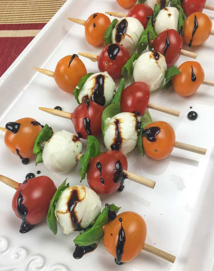 Six skewers with orange and red tomatoes, basil, small balls of mozzarella cheese and a drizzle of balsamic glaze sit on a a white platter.