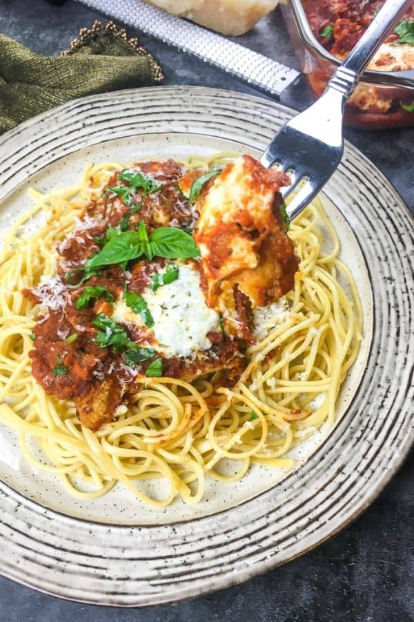 On a white plate, there's a bed of pasta. On the pasta site a piece of chicken parmesan with cheese and basil on top. There is a fork hovering above the plate with a piece of chicken on it.