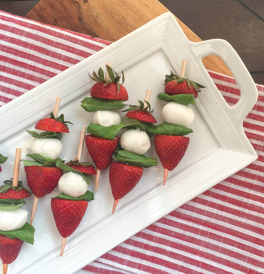 Seven skewers with strawberries, basil, and small balls of mozzarella cheese sit on a a white platter. The platter is on a red and white striped table cloth.