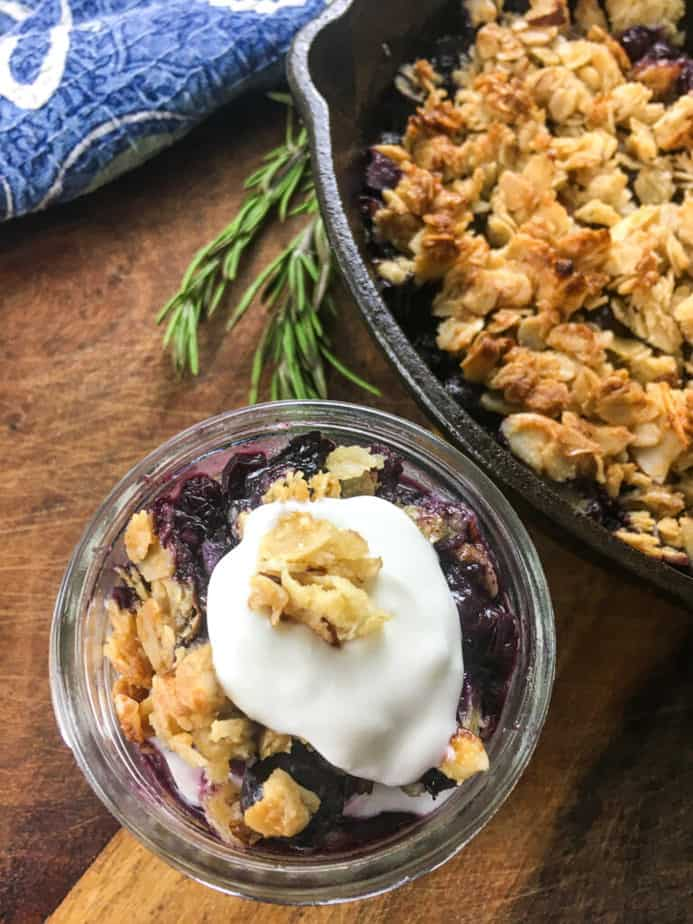 Blueberry crisp in a small mason jar with whipped cream and granola on top. The jar sits on a wooden table, next to a cast iron pan with more crisp in it.