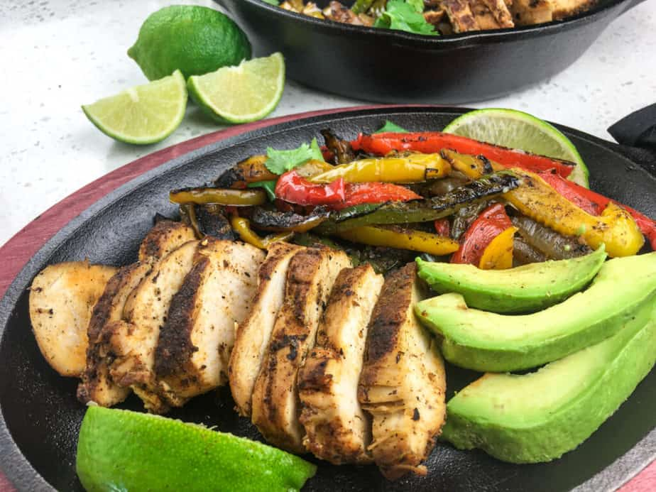 a skillet with chicken, avocado, limes and sautéd peppers