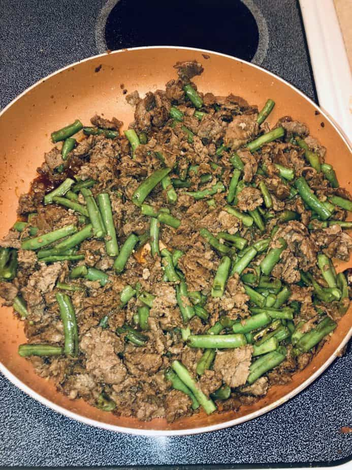 beef and green beans in a copper pan