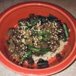 beef and green beans over brown rice, in an orange bowl