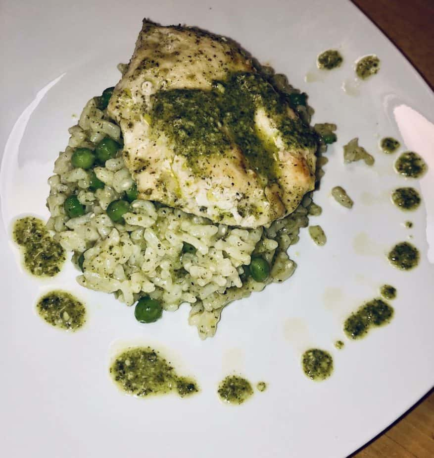 chicken breast with pesto sauce, on top of risotto. There are spots of pesto sauce on the white plate as well.