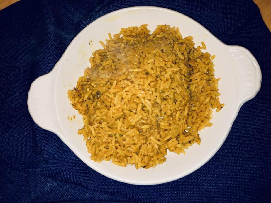 Yellow rice in a shallow white bowl on a blue background.
