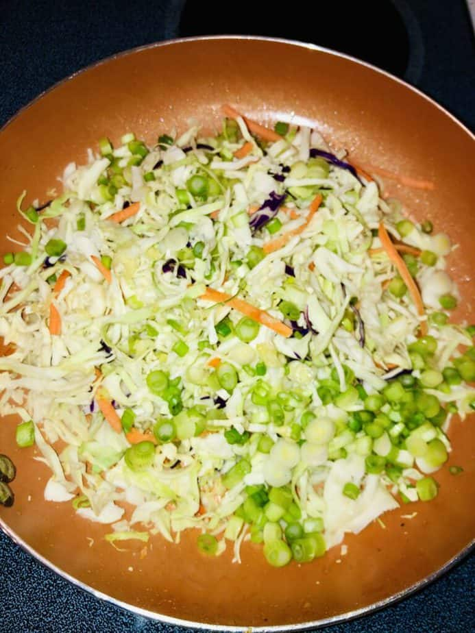 Copper pan with a shredded cabbage mix and scallions.