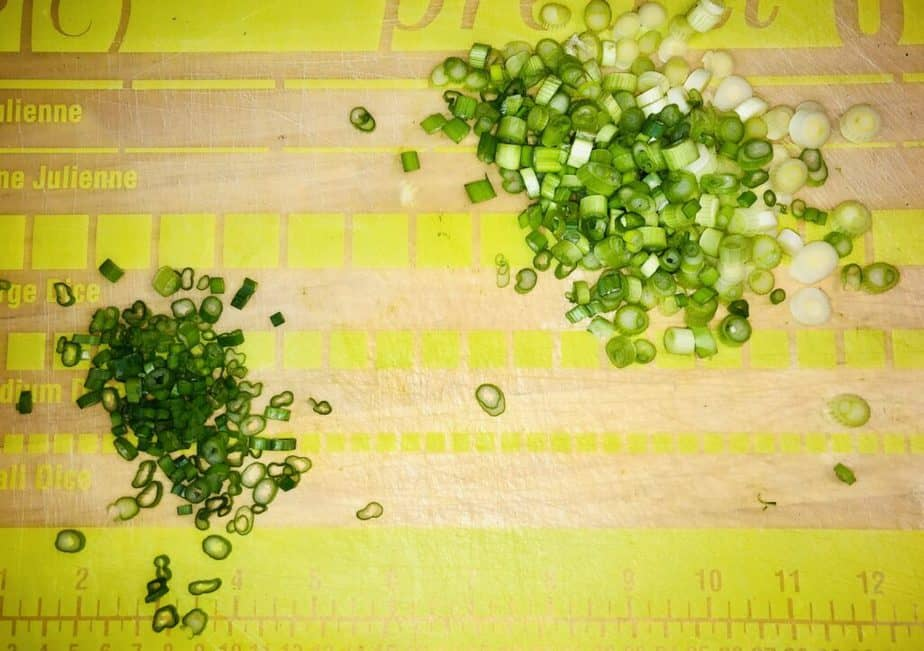Green and clear cutting board with chopped scallions on it.