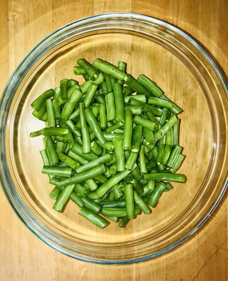 snapped green beans in a glass bowl