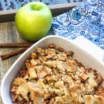apples in a baking dish with a green apple on the side of the dish
