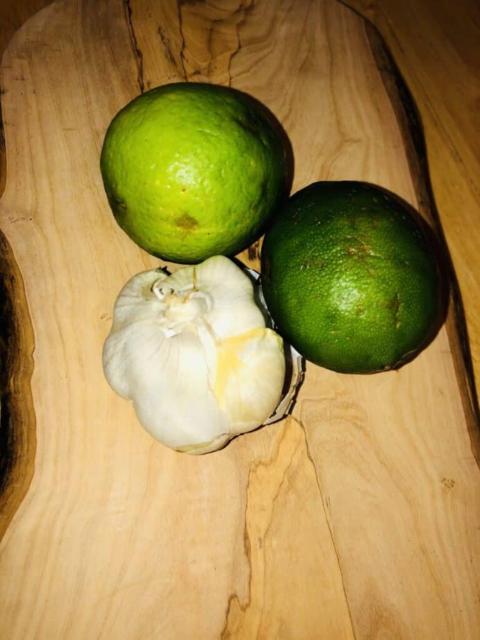 limes and a garlic bulb on a wooden cutting board