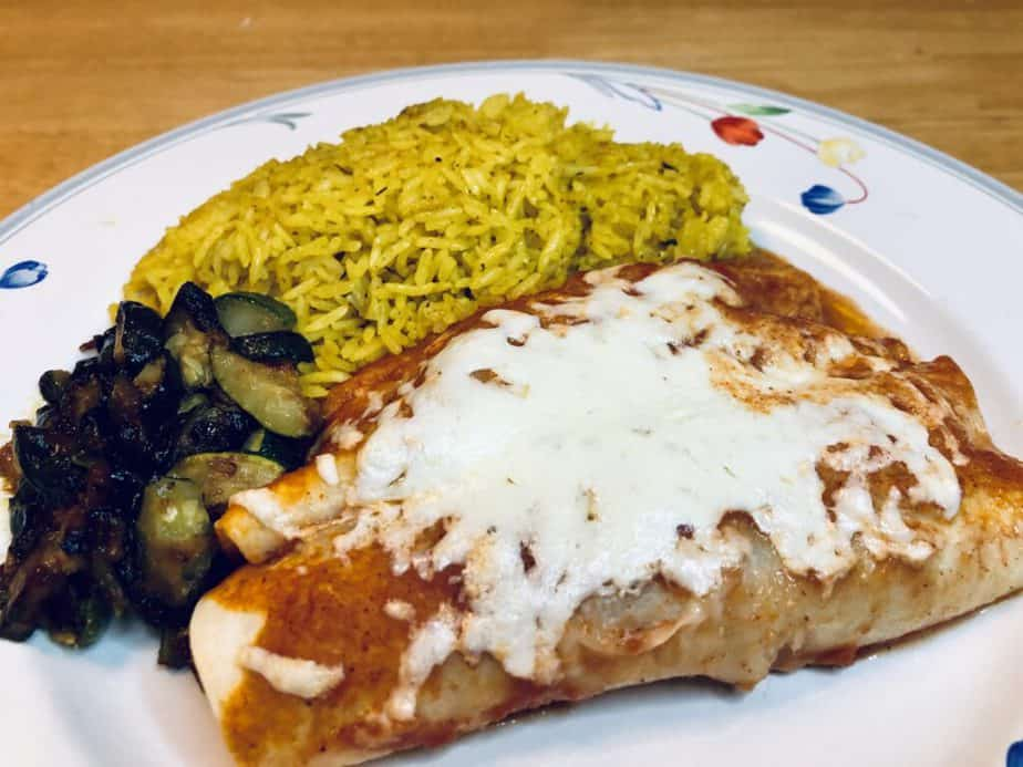 A white plate with flowers on the edge. Two cheese enchiladas, yellow rice and sautéed zucchini are on the plate