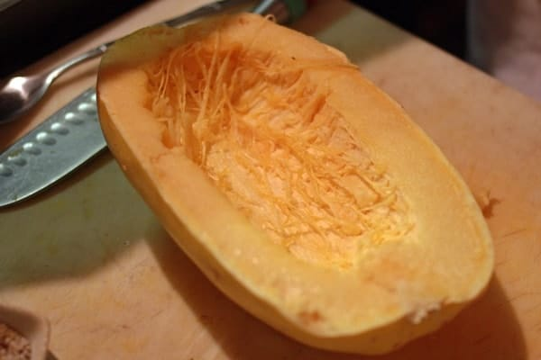 Half of a spaghetti squash on a wooden cutting board, with a carving knife  and a spoon in the background.