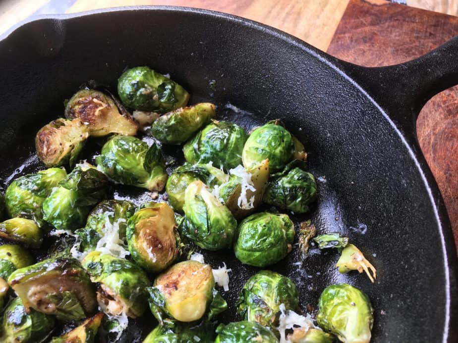 A cast-iron pan, filled with lightly browned Brussels sprouts lightly dusted with shredded cheese. The pan is on a wooden table.