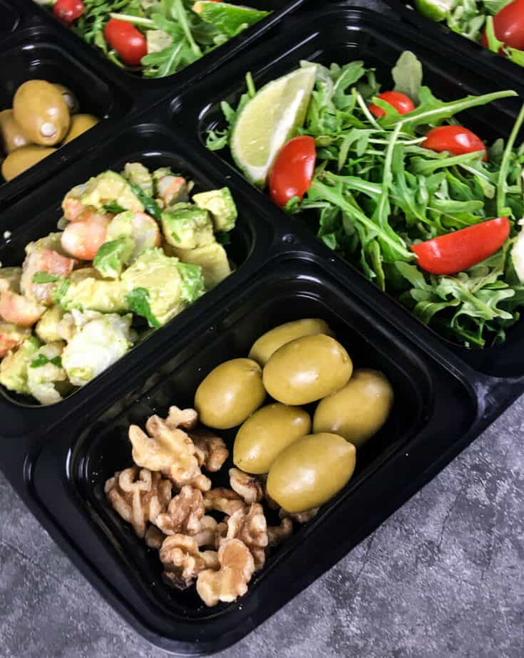 A bento box with field greens, sliced grape tomatoes and a lime wedge in one square, the keto shrimp avocado in one square, green olives and walnuts in a square, green olives in another square