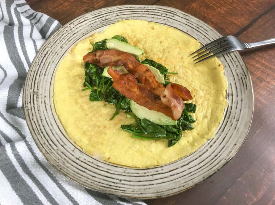 An off-white plate sits on a wooden table. There's a white napkin with grey stripes on the upper left, under part of the plate. On the plate is an open-faced egg wrap. In the middle is a pile of spinach, topped with avocado and then bacon. There's an upside down fork on the edge of the plate.