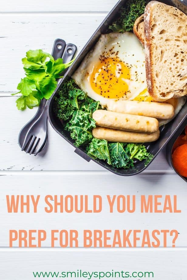 Meal Prep A black container with salad, toast and a sunny-side up egg in it. It sits on a white wooden table with a fork next to the container and greens next to that