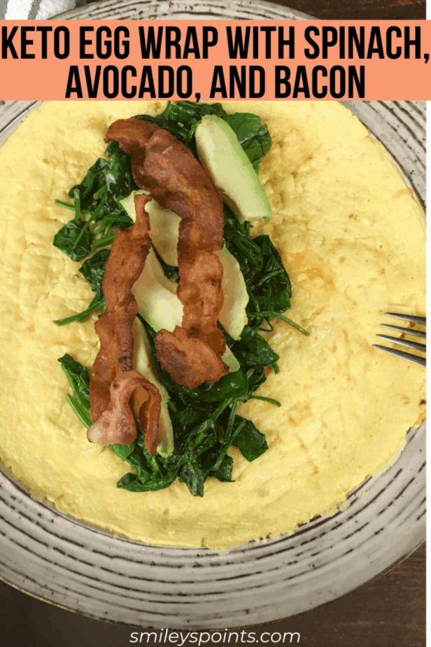 On the plate is an open-faced egg wrap. In the middle is a pile of spinach, topped with avocado and then bacon. There's an upside down fork on the edge of the plate.