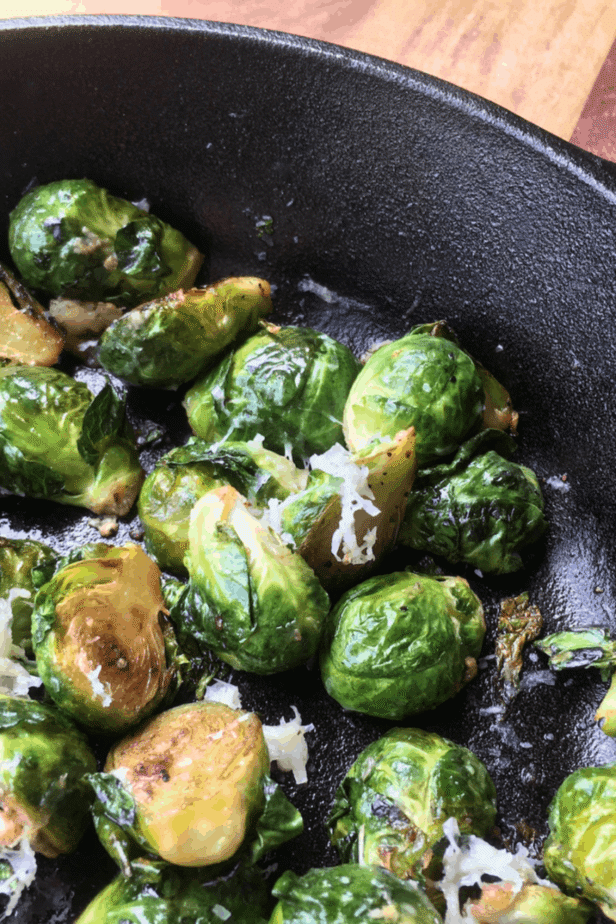 A cast-iron pan, filled with lightly browned Brussels sprouts lightly dusted with shredded cheese.