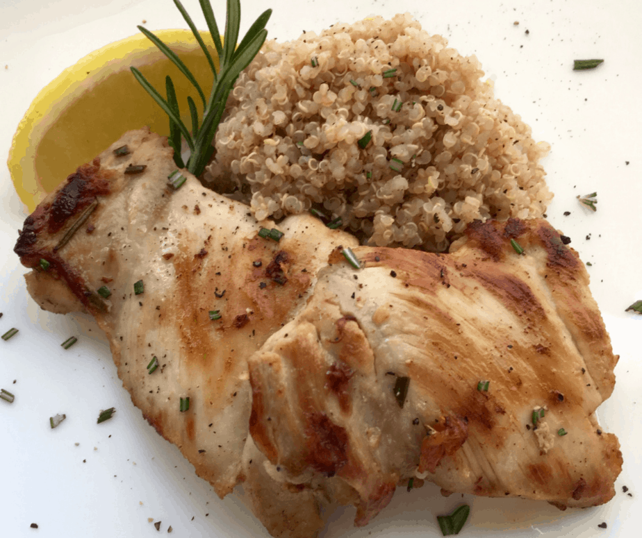 A nicely browned chicken thigh sits on a white plate. To the right is a pile of rice, on top of the rice and chicken is a sprig of rosemary and a lemon wedge.