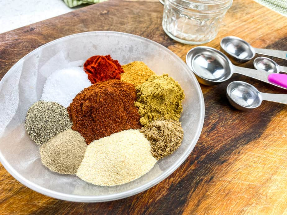 A variety of spices in a bowl and measuring spoons to the left of the bowl.