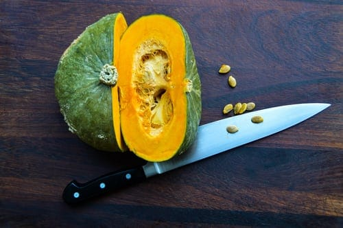 An acorn squash is cut in half, on a wooden table. The knife is under it and there are seeds on the table.