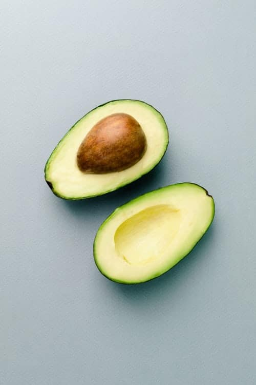 An avocado cut in half, sitting on a light grey table. There is a pit on the half on the top.