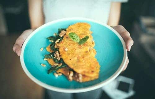 Someone is holding out an aqua plate with an omelette on it. The omelette has greens and nuts on the side.
